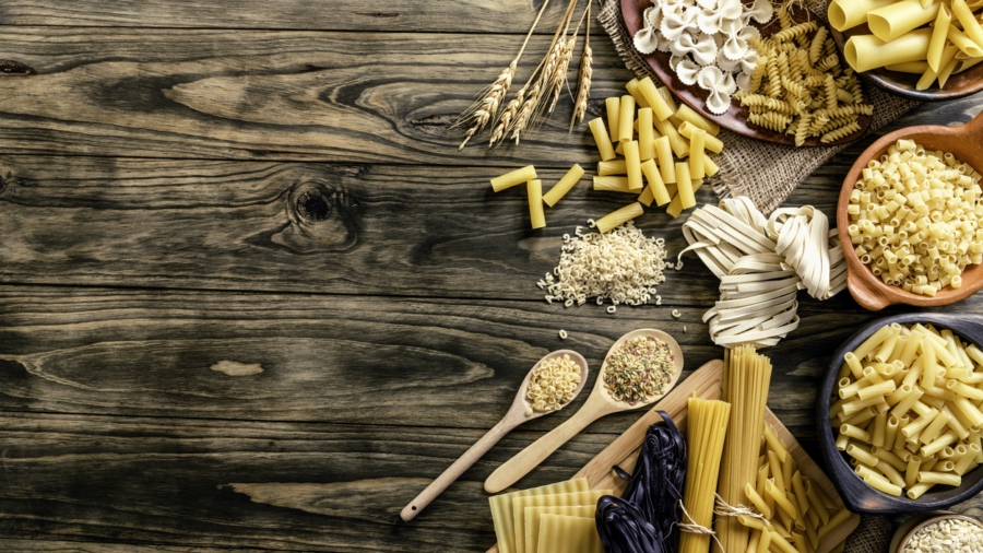 Assorted pasta including Spagetti, Linguini, Fetuccini, Farfalle, Anelli, Penne, Fusilli, Macaroni, Conchiglie, Rigatoni, Orzo,  Stortini, Letters, Vermicelli, Fetuccini, black Fetuccini and Pasticcio. Space for text on table.