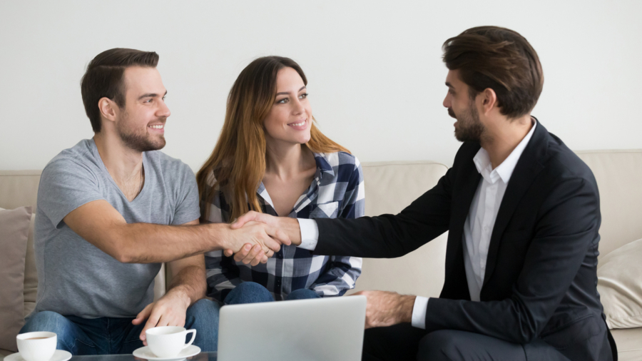Happy family couple renters tenants handshaking realtor landlord at meeting making real estate deal for apartment rent purchase, clients customers and adviser insurer shake hands, mortgage concept